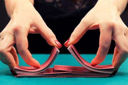 mujer sola: Mezcla tarjetas que juegan en fondo negro Foto de archivo