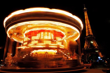 moving activity: Paris, France - September 05, 2011 : Spinnig carousel with Eiffel tower in the background during the light show [description:]Spinnig carousel with Eiffel tower in the background during the light show