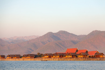 bordering: The people of Inle Lake (called Intha), some 70,000 of them, live in four cities bordering the lake, in numerous small villages along the shores, and on the lake itself. Stock Photo