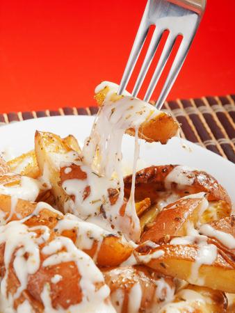 background red: Patatas al horno con mozzarella sobre fondo rojo Foto de archivo