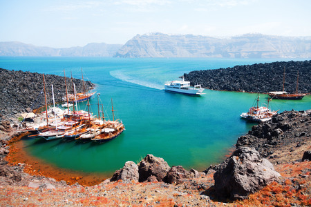 There are volcano cruises and short trips from Fira with a boat and a lot of tourists visit the volcanic landscape Reklamní fotografie