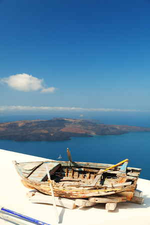 firostefani: Old boat on the roof of a private villa in Firostefani, Santorini, with a perfect view of the volcanic island
