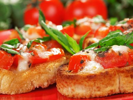 Bruschetta with tomato and mozzarella cheese, decorated with basil photo