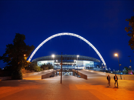 wembley: London, United Kingdom - May 22, 2009 : Brightly lit Wembley Stadium at night with people in front [description:]Wembley Stadium in London at night