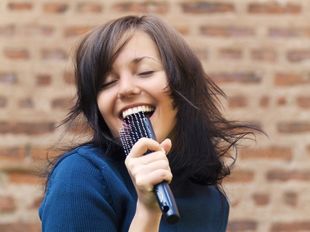 singing: Young tousle-headed brunette pretending to sing with her hair brush as a microphone Stock Photo
