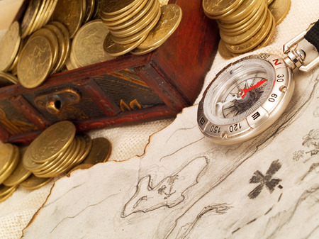 Treasure chest with gold coins, treasure map and compass