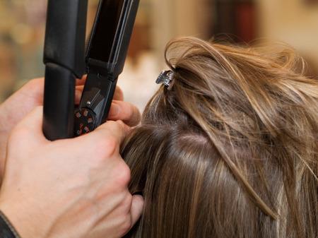 straightener: Using hair straightener Stock Photo