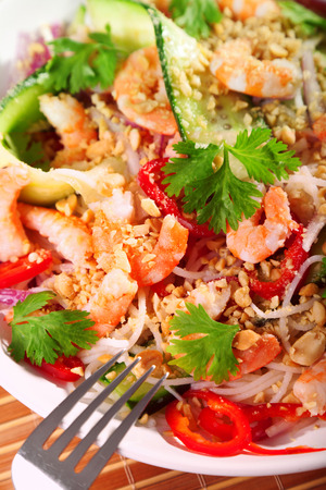 Asian salad with rice noodles, shrimps, peanuts, peppers, cucumber and cilantro photo