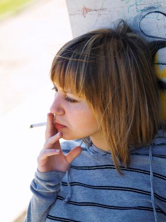 late twenties: Young student smoking in front of her school