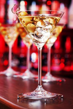 martini glasses: Several glasses of famous cocktail Martini, shot at a bar