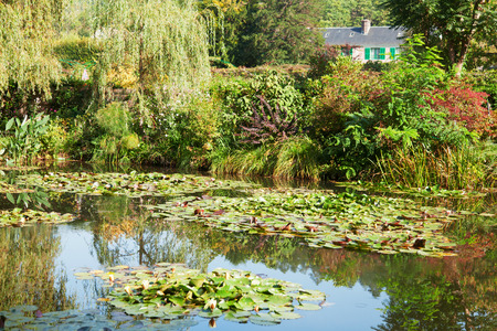 monet: Monets water lily pond made by Clode Monet himself - this scenery has been inspiration for a lot of his impressionistic artwork, His house painted in pink and green, his favourite colors, is seen in the background. Stock Photo