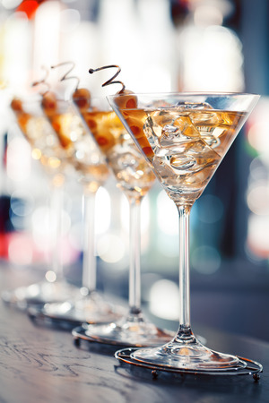 Several glasses of famous cocktail Martini, shot at a bar with shallow depth of field  Ingredients:  55 ml gin  15 ml dry vermouth  olives to garnish Stock Photo