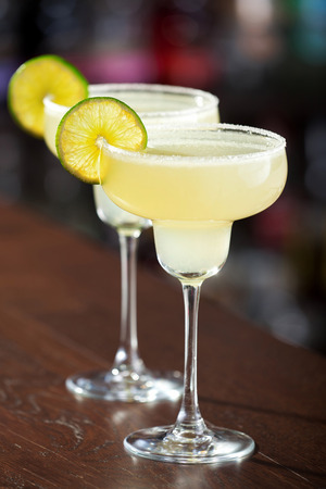 margarita glass: The margarita is a cocktail consisting of tequila mixed with orange-flavoured liqueur and lime or lemon juice, often served with salt on the glass rim. Stock Photo