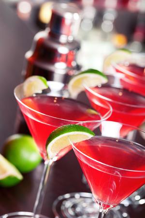 cocteles: Cuatro c�cteles cosmopolitas de frente, botellas borrosas de bebidas alcoh�licas en el fondo.