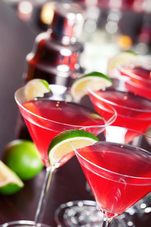 cocktail: Four cosmopolitan cocktails in front, blurred bottles of alcoholic drinks in the background. Stock Photo