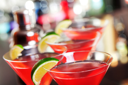 cosmopolitan: Four cosmopolitan cocktails in front, blurred bottles of alcoholic drinks in the background. Stock Photo