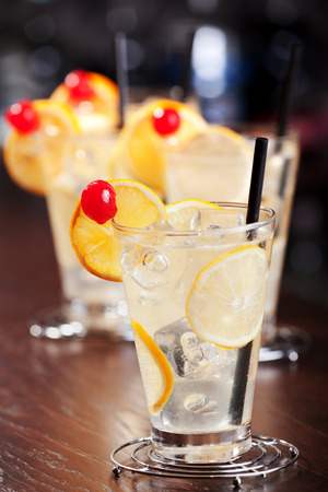 tom collins: Four glasses of Tom Collins cocktail at a bar.