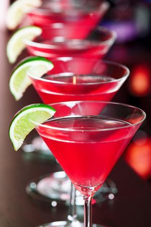 Vier kosmopolitischen Cocktails vor, verschwommenes Flaschen alkoholische Getränke im Hintergrund.