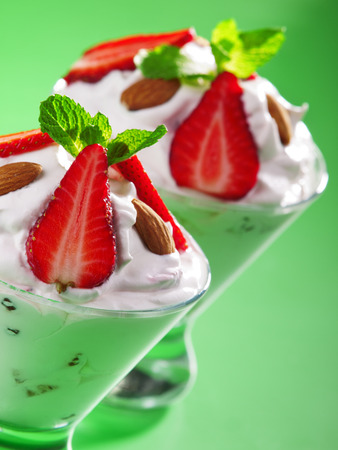 garnished: Strawberry cream in a glass garnished with strawberries, almonds and fresh mint
