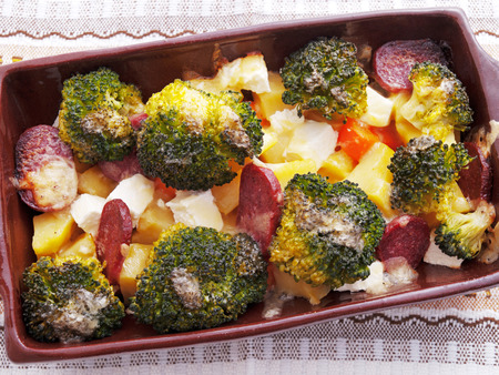 Brocolli and potato casserole in a baking dish on the table Фото со стока