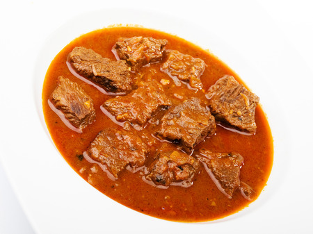 Beef goulash in a plate, isolated on white photo