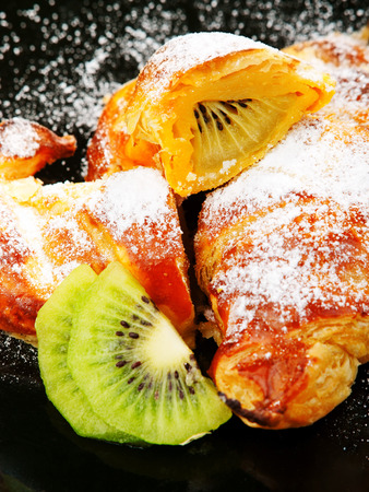 caster: Croissants with kiwi fruit and caster sugar Stock Photo