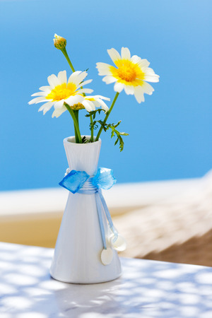 fullframe: Vase with flowers on a table with a sea view in a restaurant in Oia, Santorini Stock Photo