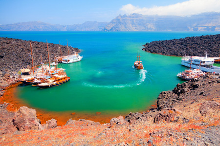 There are volcano cruises and short trips from Fira with a boat and a lot of tourists visit the volcanic landscape Stock Photo