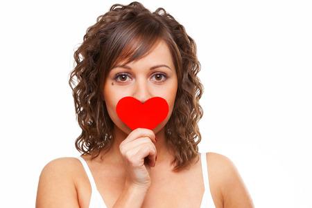 Junge attraktive Frau mit roten Papier Herz wie ein Valentinsgrußkarte und verbarg ihr Gesicht