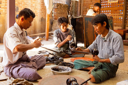 lacquerware: Bagan, Myanmar - February 25, 2011 : Young Burmese men working on lacquerware souvenirs such as plates, dishes, jewelry boxes and even furniture. [description:]Yun-de is lacquerware in Burmese, and the art is called Pan yun. The lacquer is the sap tapped  Editorial