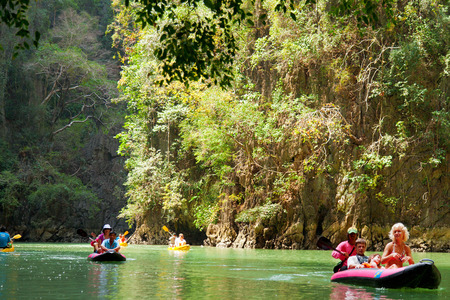 "accessed: Pang Nga, Thailand - March 16, 2011 : Group of tourists kayaking in the hongs of Pang Nga Bay [description:]The ""hongs"" are actually collapsed cave systems in the interior of each island, only accessed by tough, purpose-designed inflatable can"