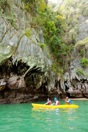 """accessed: Pang Nga, Thailand - March 16, 2011 : Couple of tourists kayaking in the hongs of Pang Nga Bay in the morning. [description:]The """"hongs"""" are actually collapsed cave systems in the interior of each island, only accessed by tough, purpose-designed"""