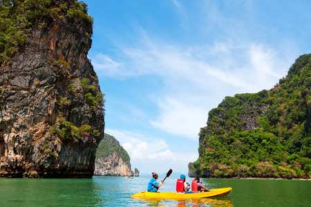 """accessed: Pang Nga, Thailand - March 16, 2011 : Couple of tourists kayaking in the hongs of Pang Nga Bay in the morning. [description:]The """"hongs"""" are actually collapsed cave systems in the interior of each island, only accessed by tough, purpose-design"""