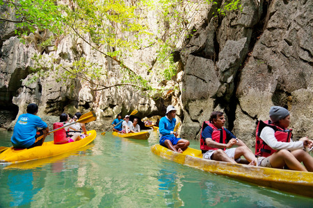 """accessed: Pang Nga, Thailand - March 16, 2011 : Group of tourists kayaking in the hongs of Pang Nga Bay [description:]The """"hongs"""" are actually collapsed cave systems in the interior of each island, only accessed by tough, purpose-designed inflatable can"""