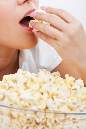 palomitas de maiz: Mujer joven de comer palomitas de ma�z aislados en el fondo blanco