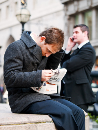 magistrates: London, United Kingdom - July 17, 2013 : Two young businessmen staying in front of City of London Magistrates Court. One of them is reading a newspapper while the other is talking on a mobile phone