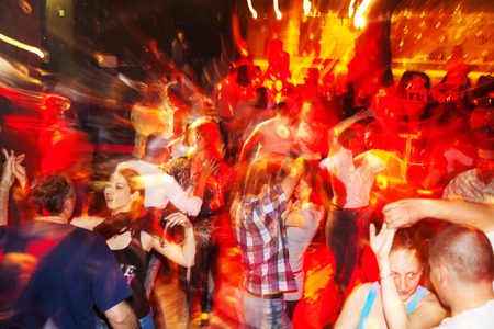 action blur: Sofia, Bulgaria - April 26, 2011: Social salsa dancing in a nightclub. A lot ot young couples enjoy the rythms of salsa, bachata, cha-cha-cha and merengue