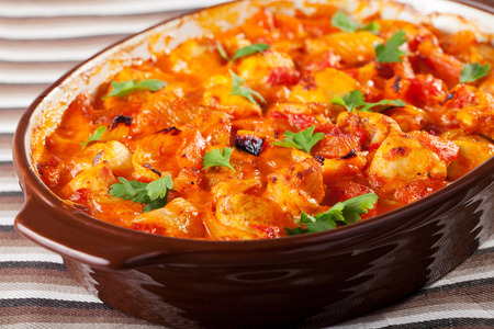 Casserole with chicken, potatos and tomatos in a baking dish, ready-to-eat Stock Photo