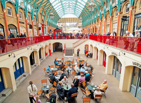 covent garden market: London, United Kingdom - April 21, 2012 : Covent Garden enclosed market with cafes and restaurants with a lot of shopping people inside, sometimes there are street musicians and other performers Editorial