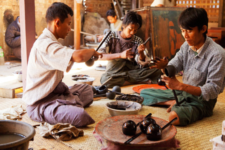 lacquerware: Bagan, Myanmar - February 25, 2011 : Young Burmese men working on lacquerware souvenirs such as plates, dishes, jewelry boxes and even furniture.