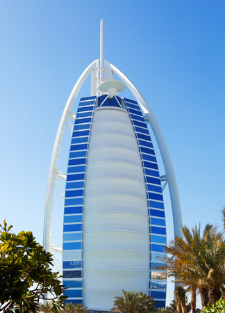 full lenght: Dubai, United Arab Emirates - March 23, 2011 : Full lenght view of Burj Al Arab, one of the Dubai landmarks with its visitors going to the beach in the afternoon