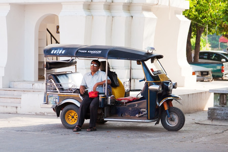 tuktuk: Chiang Mai, Thailand - March 06, 2011 : Thai man sitting in his tuk-tuk while waiting for the tourists to come