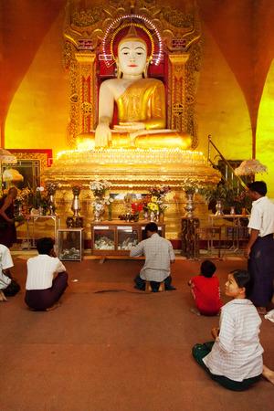 sitting on the ground: Mandalay, Myanmar - February 28, 2011 : Burmese men and women sitting on the ground and praying in a pagoda