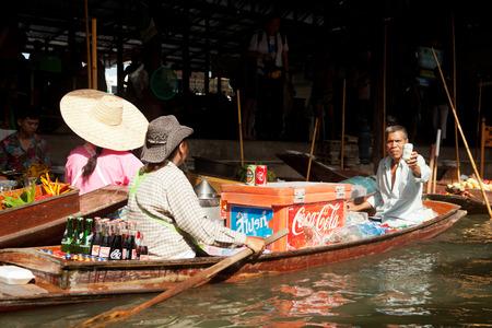 damnoen saduak: Damnoen Saduak, Thailand - March 21, 2011 : Senior Thai man selling refreshment drinks for tourists on a boat in Damnoen Saduak Floating Market Editorial
