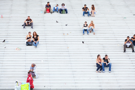 Paris, France - September 02, 2011 : Young people sitting at the stairs of La Defance in Paris talking and looking at the magnificent view of the city