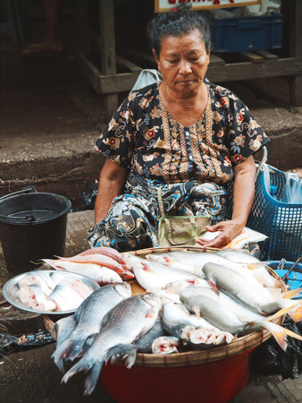 burmese: Yangon, Myanmar - February 24, 2011 : Senior Burmese woman selling fresh fish in the street market. Editorial