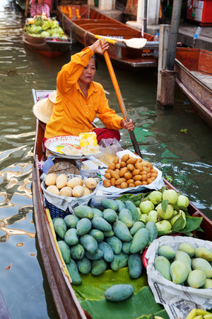 damnoen saduak: Damnoen Saduak, Thailand - March 21, 2011 : Senior Thai woman with a hat on a boat full of fruits in Damnoen Saduak Floating Market Editorial