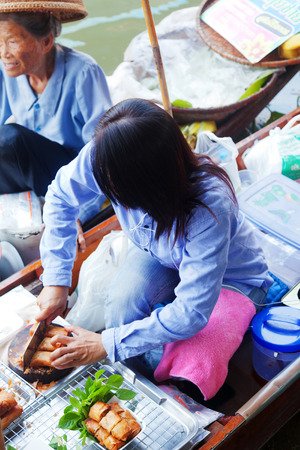 saduak: Damnoen Saduak, Thailand - March 21, 2011 : Young Thai woman selling freshly cooked food on a boat in Damnoen Saduak Floating Market