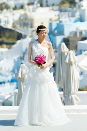 Firostefani, Greece - May 05, 2012 : Young asian bride on a photo session early in the morning before the tourist are on the streets.