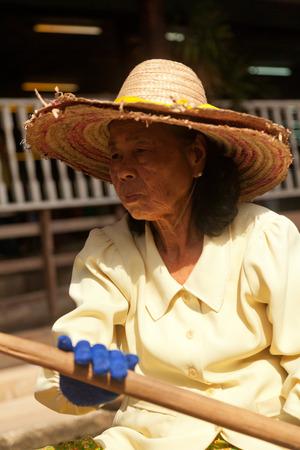 damnoen saduak: Damnoen Saduak, Thailand - March 21, 2011 : Senior Thai woman with hat selling freshly cooked food and fruits on a boat in Damnoen Saduak Floating Market